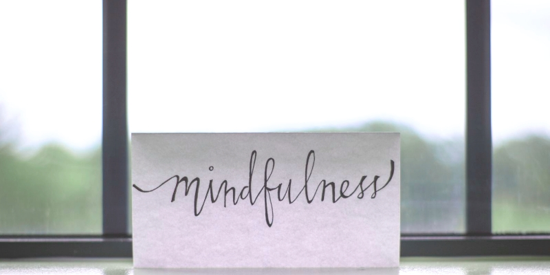 """White paper propped against window with the word """"Mindfulness"""" written in calligraphy"""