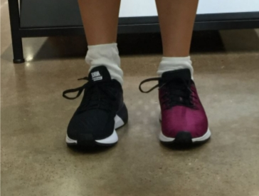 Trying on shoes. Right shoe is pink and shows pronation. Left shoe is black and has more structure.