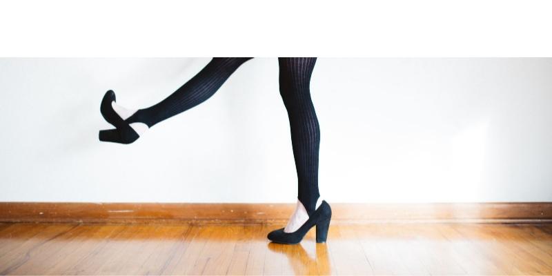 Legs in black tights and black pumps walking across wood floor