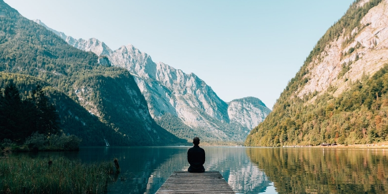 man sitting at the end of a lake dock viewing the mountains in the distance