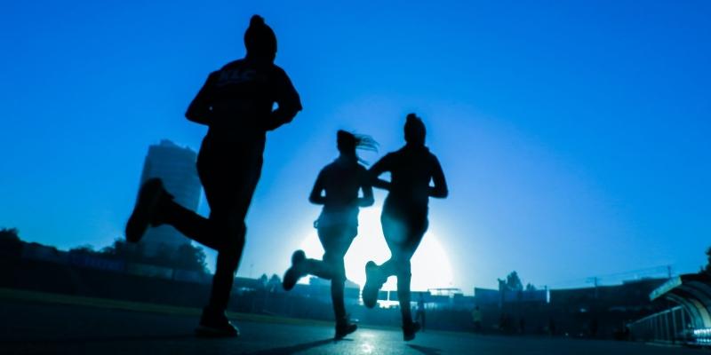 Silhouette of three women running on asphalt