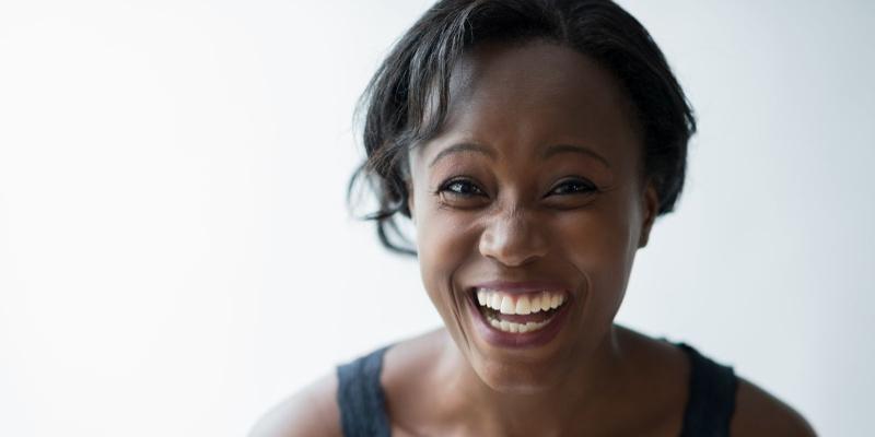 Dark-skinned female smiling in front of white background