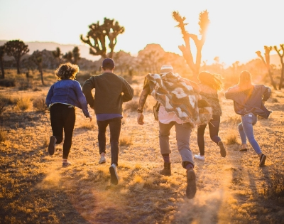 Group of young people running towards trees at sunset